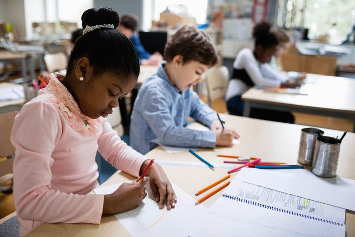 Serious students studying at desk in classroom
