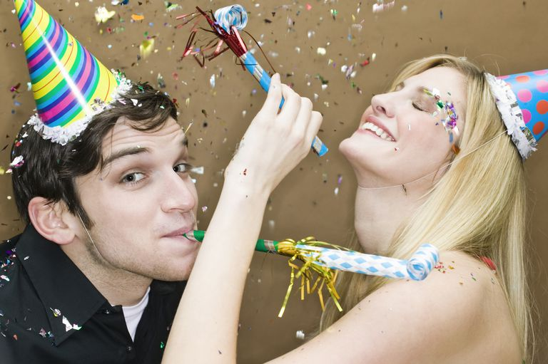 Couple wearing party hats, with blowers