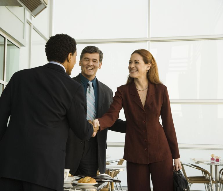A woman being introduced by one man to another in a business setting.