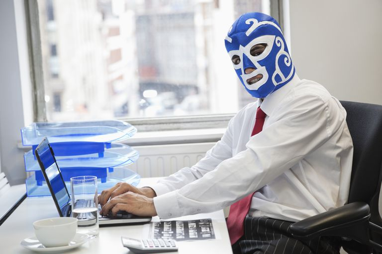 Portrait of businessman using laptop while wearing wrestling mask at office desk