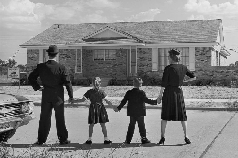image of a family of four holding hands while standing in a line with their backs - 1950 Style Home Plans