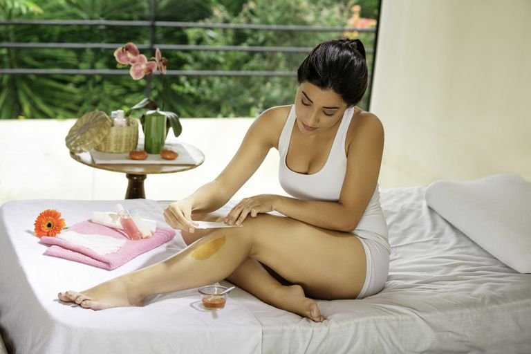 Hispanic young woman using depilation wax on her legs