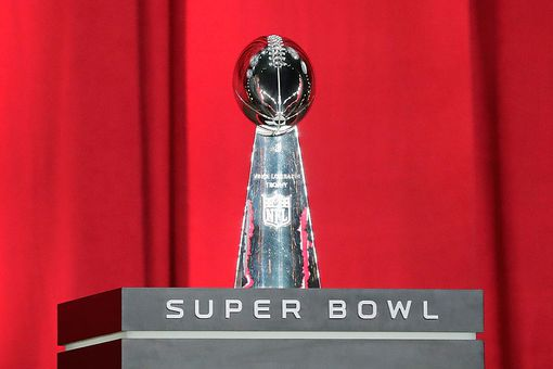 Super Bowl Lombardi Trophy on display with red curtains in background.