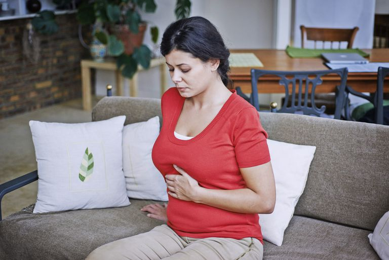 Woman suffering from abdominal pain, France