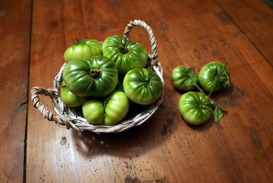 High Angle View Of Fresh Green Tomatoes In Basket And Table