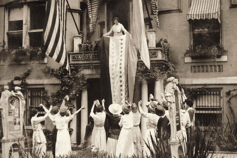 Alice Paul on balcony, fellow suffragists celebrating suffrage victory, 1920