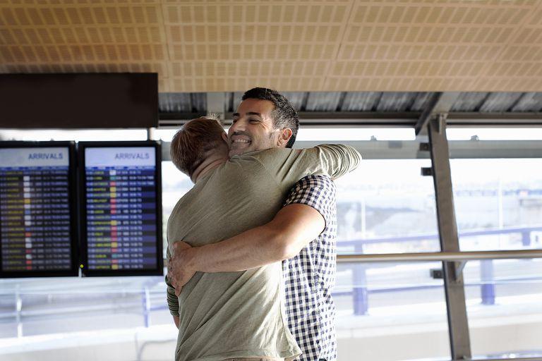 Two gay men embracing at airport
