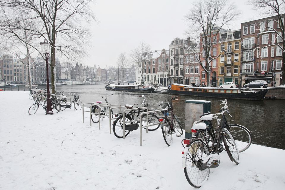 Bicycles parked at Amstel riverbank convered in snow with Dutch bungalos and houses boats in the background covered in snow in Amsterdam,Netherlands