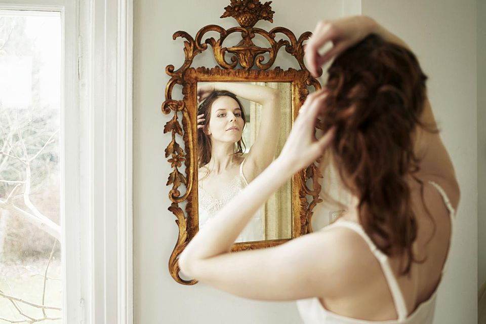 Young woman looking in mirror, fixing hair (over the shoulder view)
