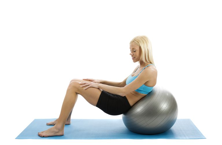 A woman exercising on a ball has her pelvis in posterior tilt.