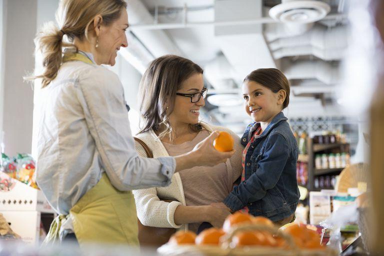 Worker giving orange to girl in market