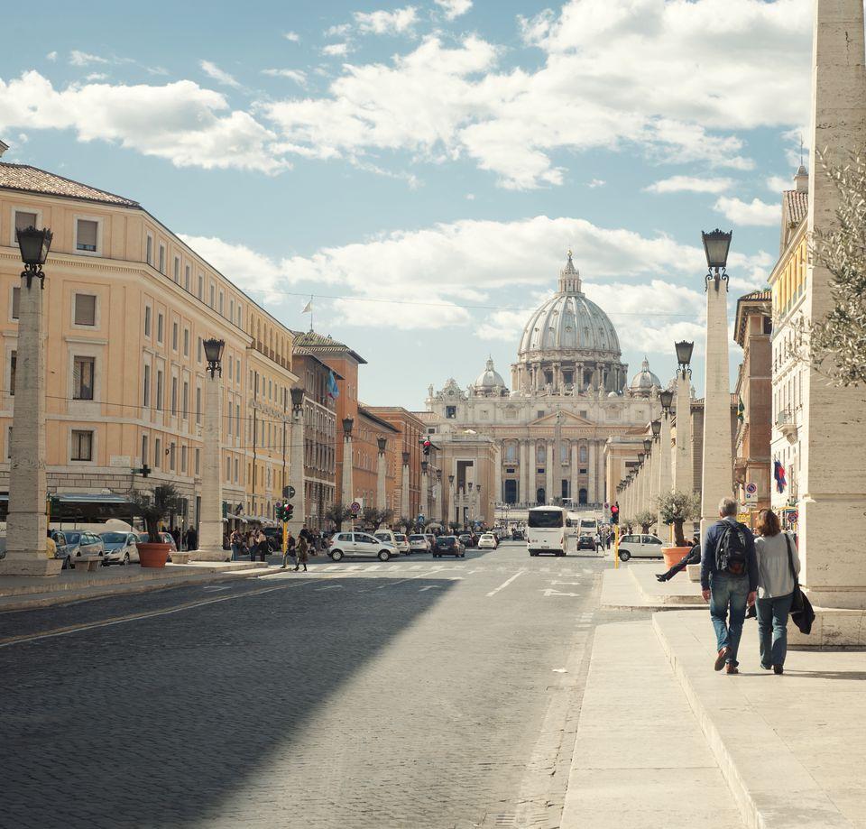 Couple walking on sidewalk in Rome