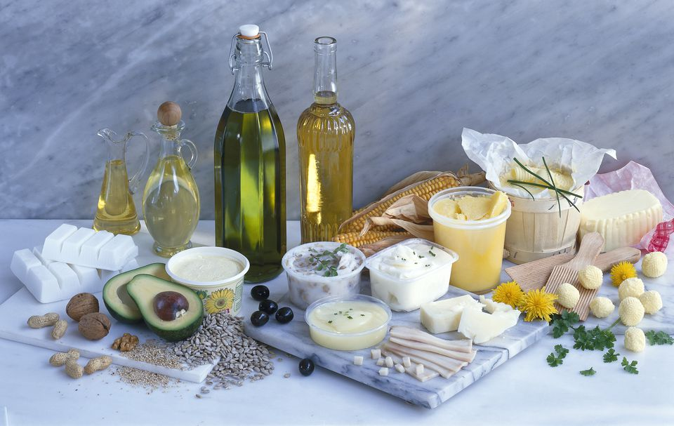 Chopping board, oil bottles and different types of cooking fat