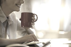 Woman at keyboard with coffee cup