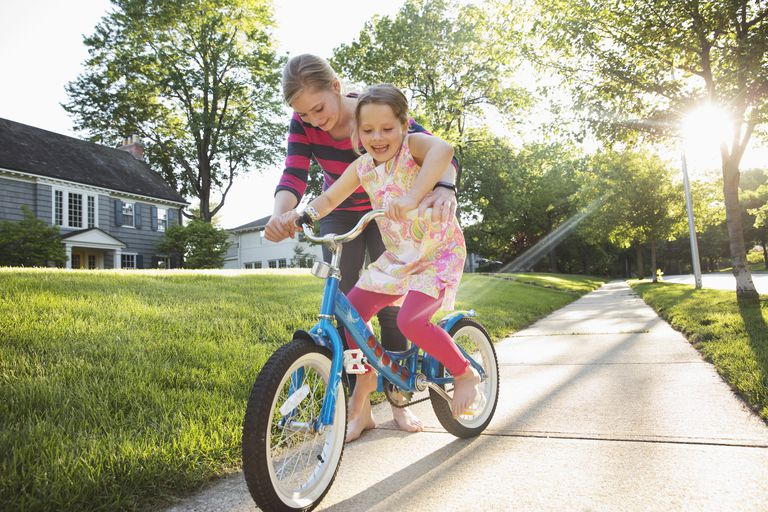 Babysitter teaching little girl how to ride a bike