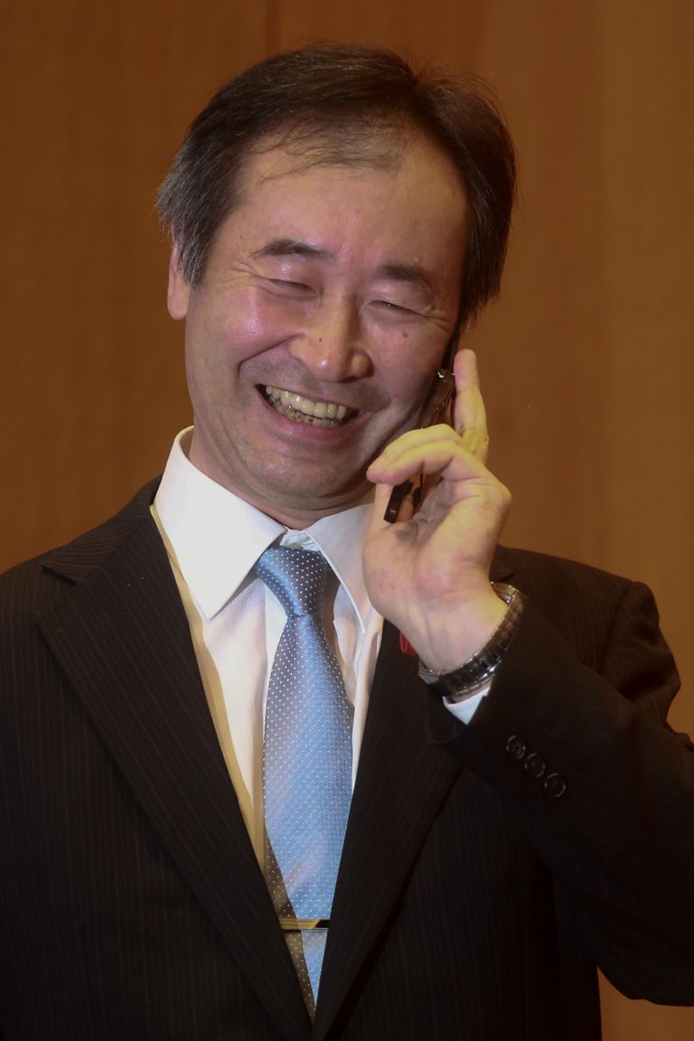 Picture of a Japanese man in his mid-fifties, in a suite with a blue tie, smiling while talking on a cellphone.