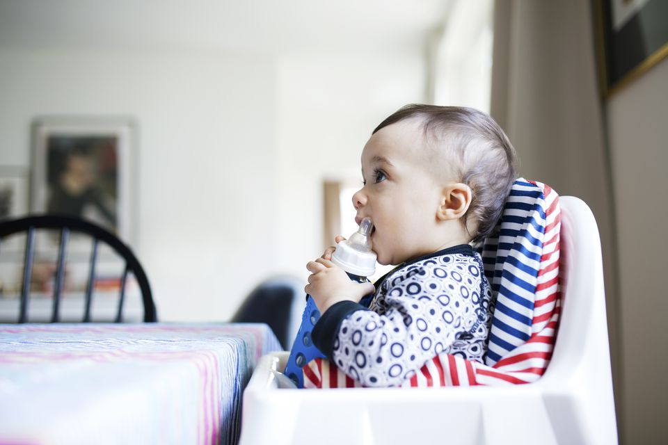 Side view of baby girl drinking milk from bottle while sitting on high chair