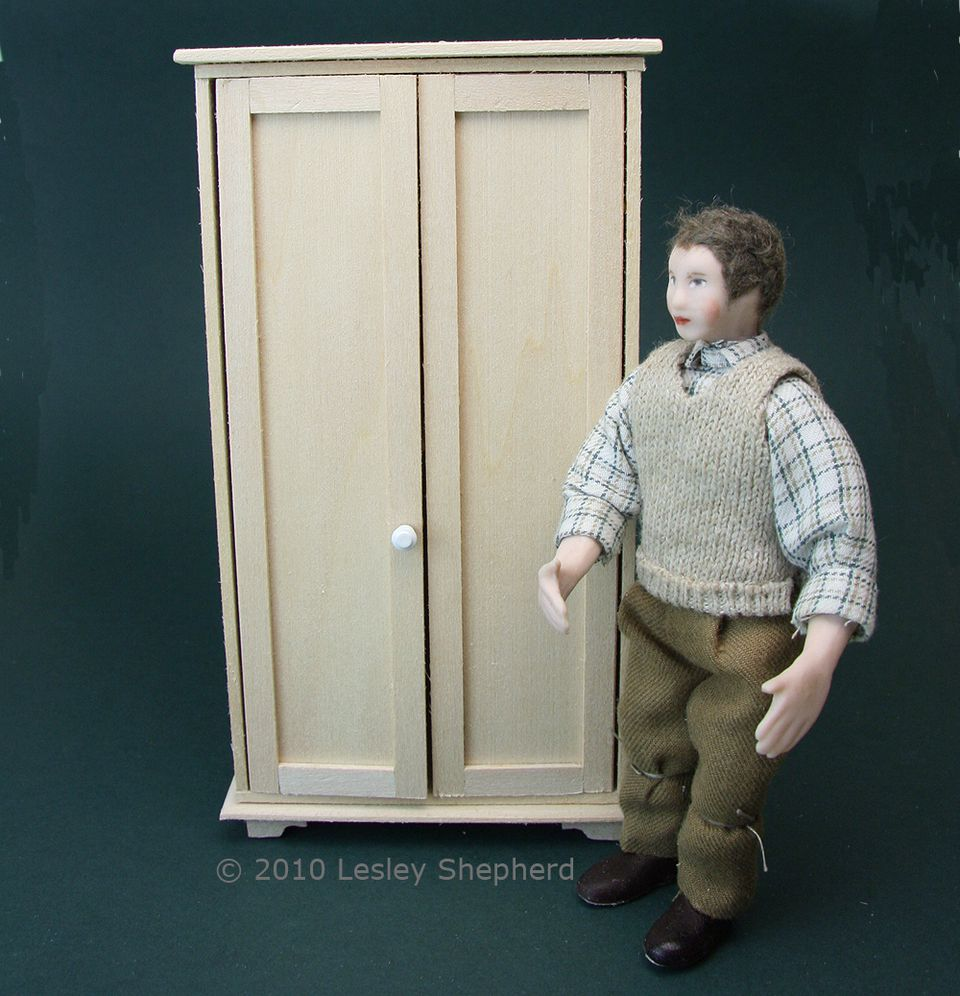 A simply constructed dolls house scale armoire with shaker doors is shown beside a doll for scale