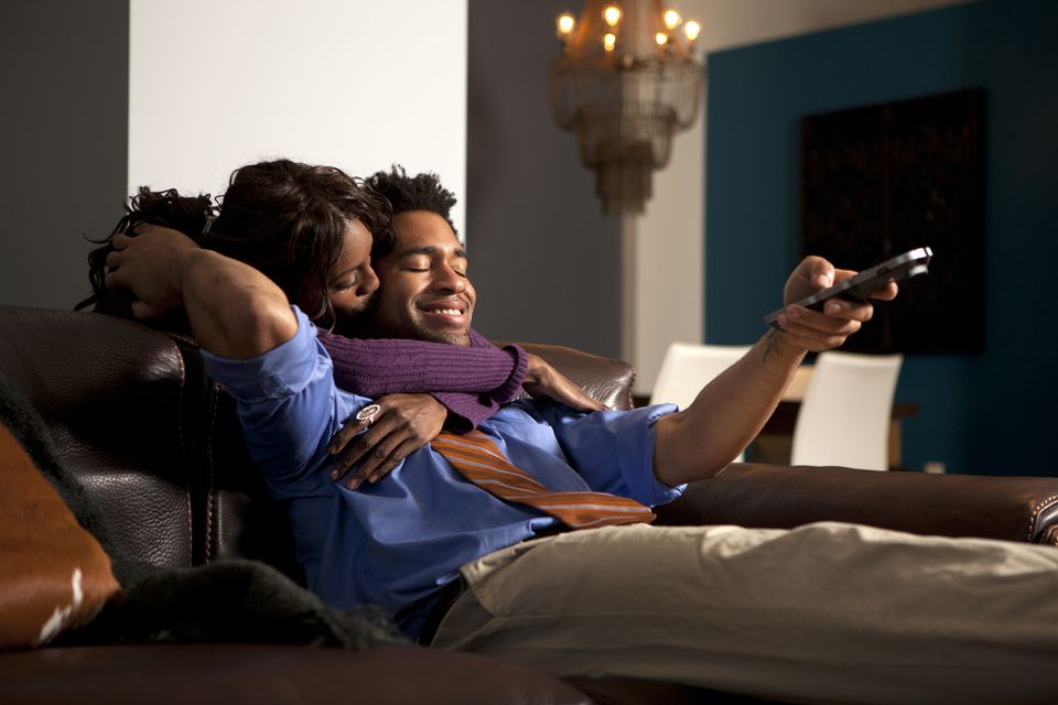 Woman kissing a man watching television.