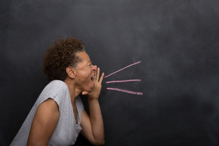 Senior woman in front of blackboard pretending to shout