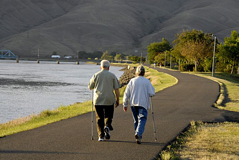 Two elderly people walking a path along a river