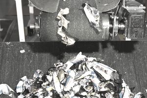 Shredded material coming off a conveyor.