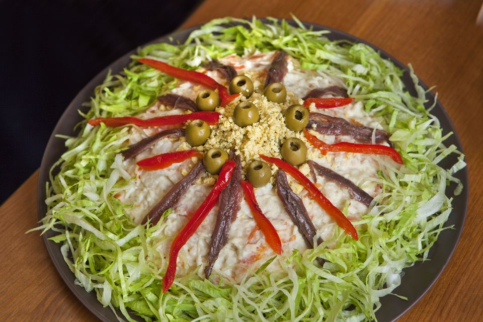 Ensalada Rusa topped with peppers and olives