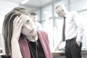 Female executive looking sad in an office with her colleagues discussing in the background