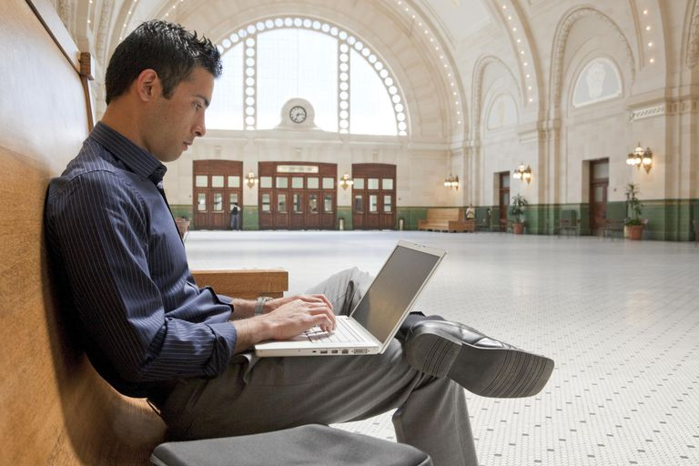 Businessman using laptop in train station