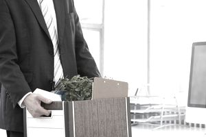 businessman carrying file box of belongings