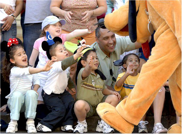 Youngsters reaching out to Pluto during a Disney parade.