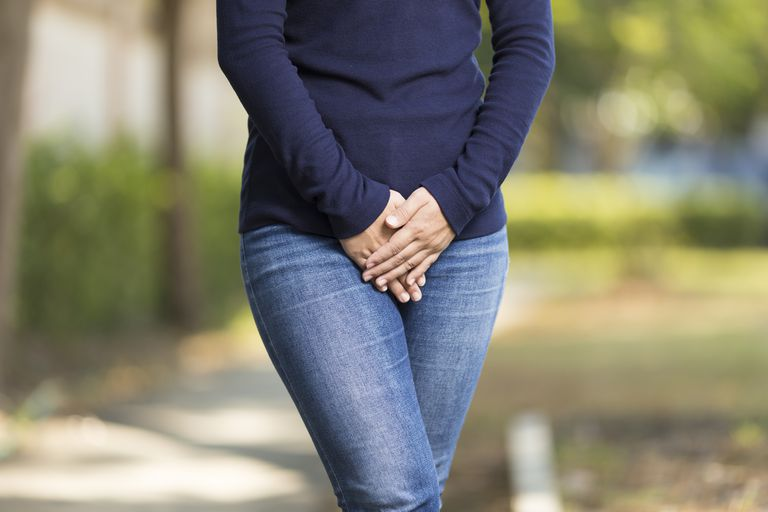 woman experiencing pelvic pain wondering about the signs and symptoms of cervical cancer