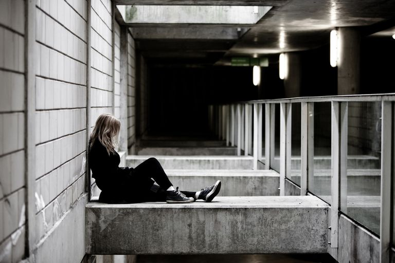 A depressed young woman sits alone against a concrete pillar. Denmark