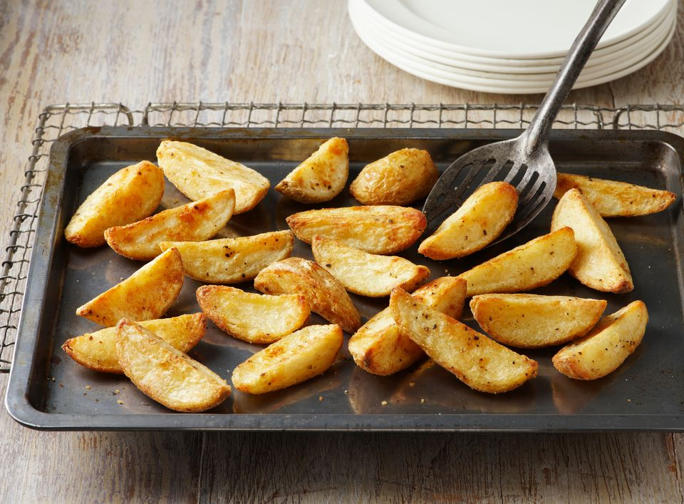 Seasoned potato wedges. Seasoned with salt and pepper on baking tray and wire rack