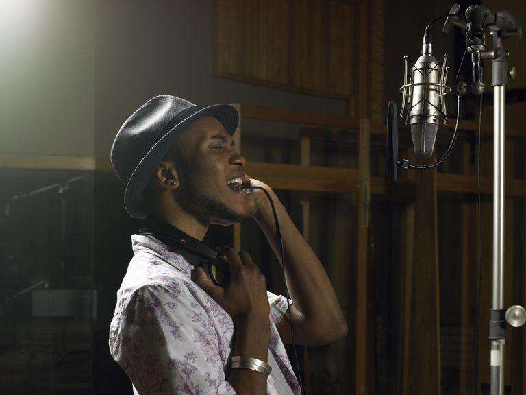 man singing in recording studio booth