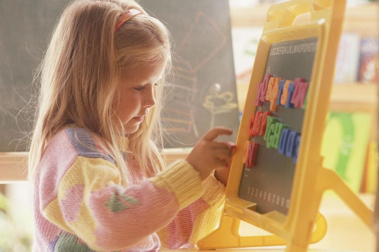 Girl playing with magnetic letters