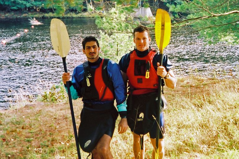 Two paddlers show off their kayak equipment.