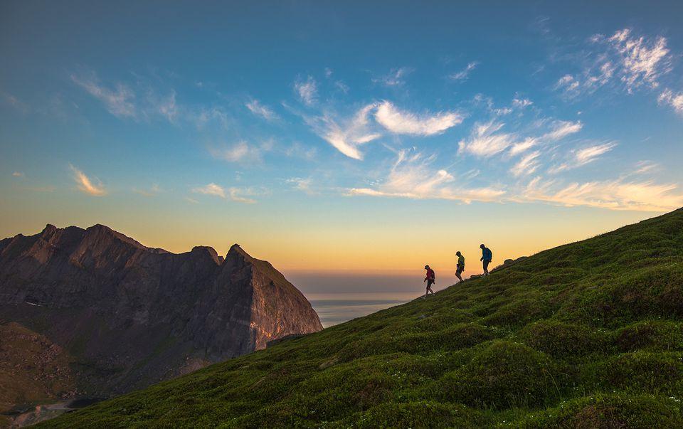 Norway, Flakstad Island, Tourist hiking on Mt Ryten