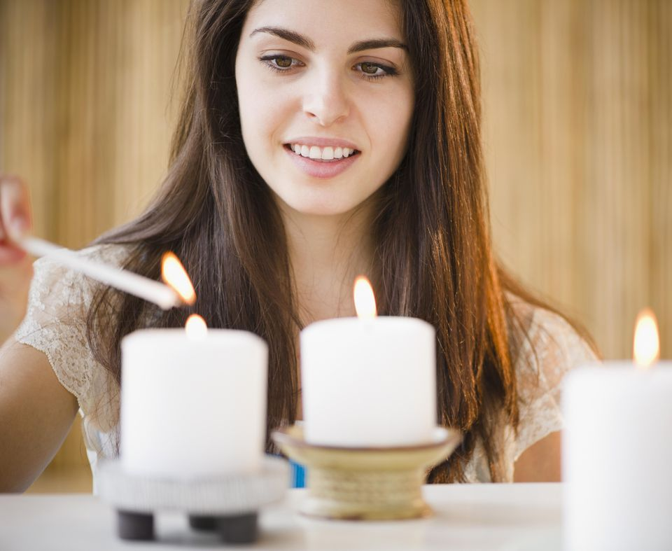 Young woman lighting candles
