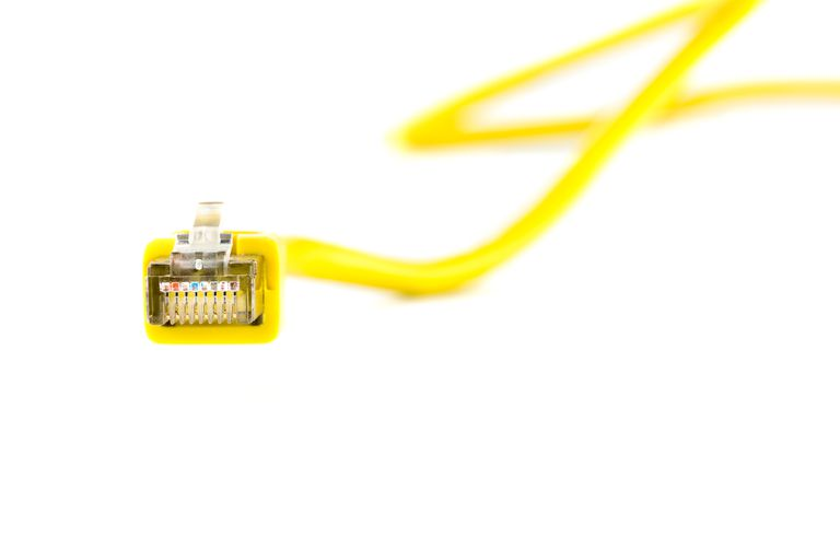 Close-Up Of Yellow Network Connection Plug Over White Background