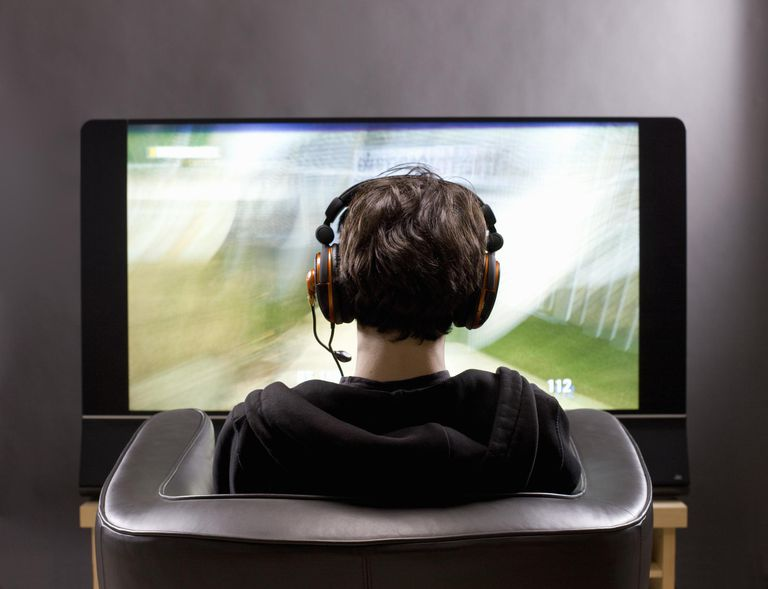 Teenage boy sits in front of TV playing video game