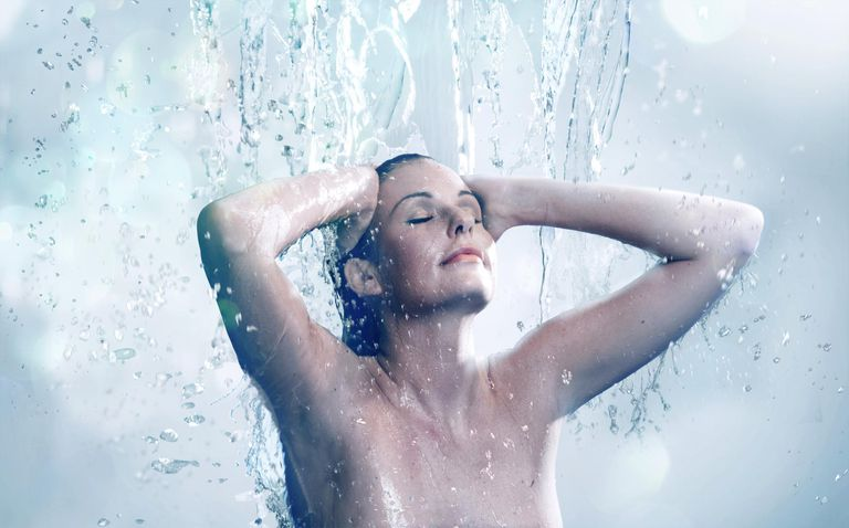 Beautiful woman bathing under running water