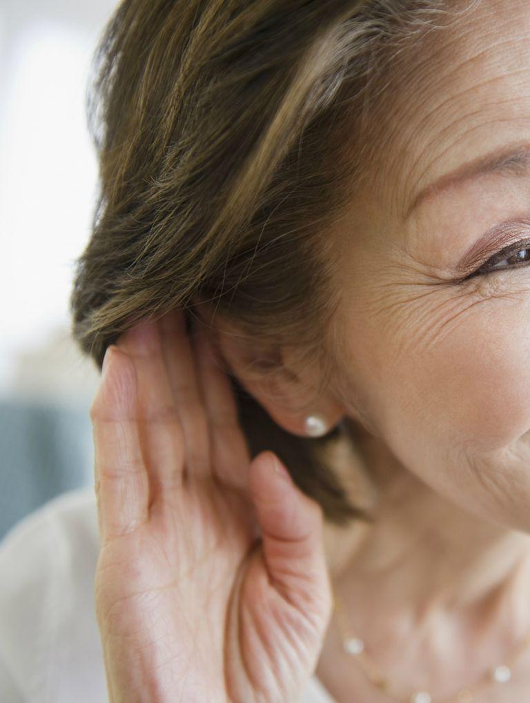 Woman listening with hand near ear