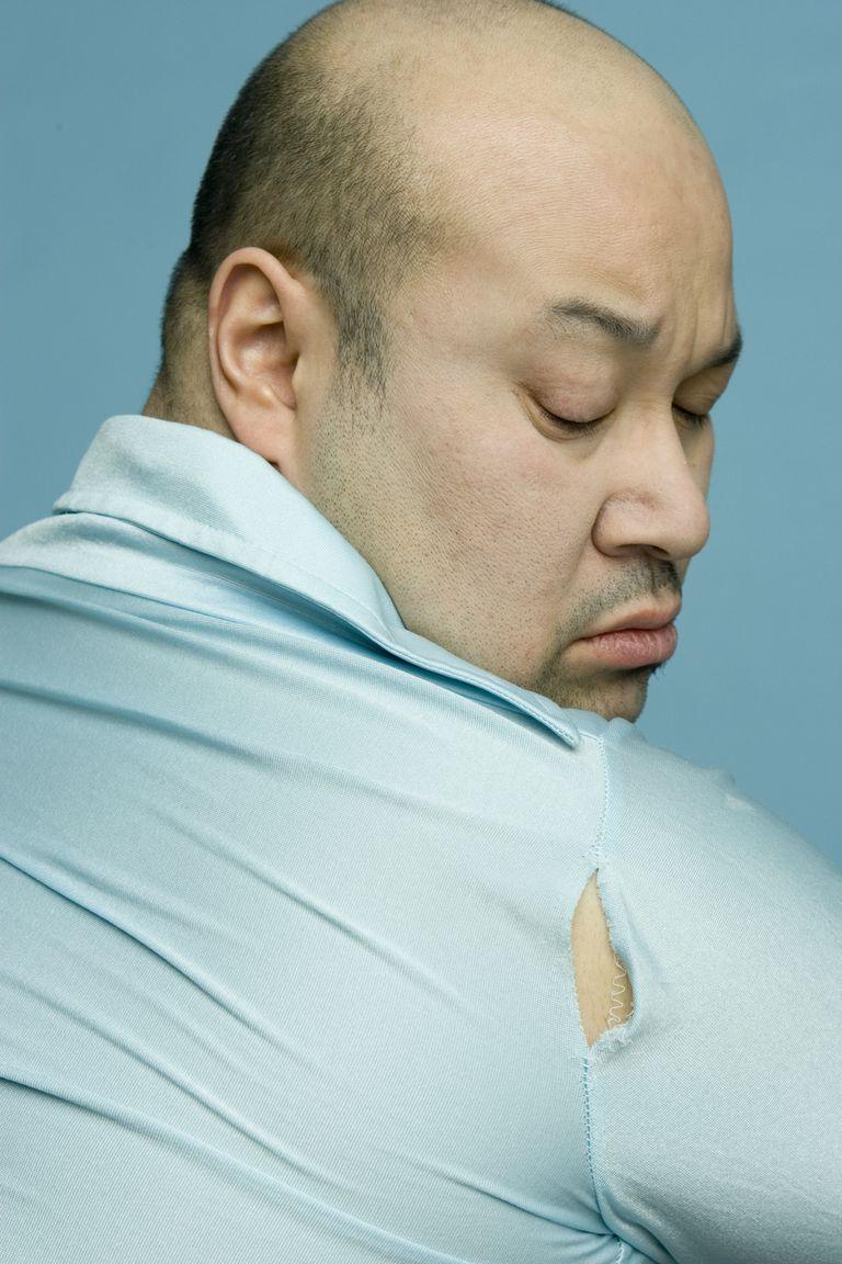 A man's shirt rips at the arm seam.