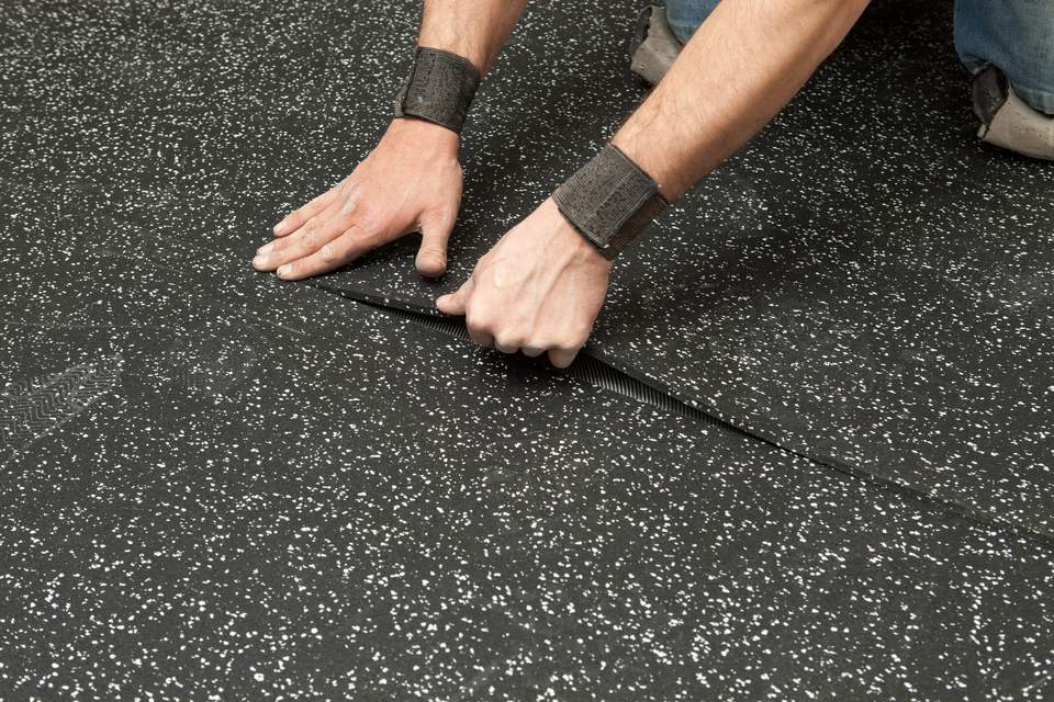 Worker Installing Recycled Rubber Floor