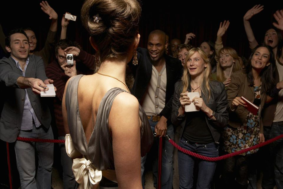 Female celebrity in evening dress talking to fans behind rope barrier