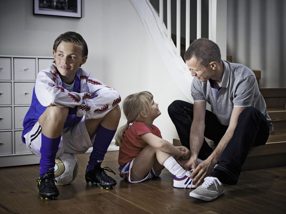 A picture of a dad getting his kids ready