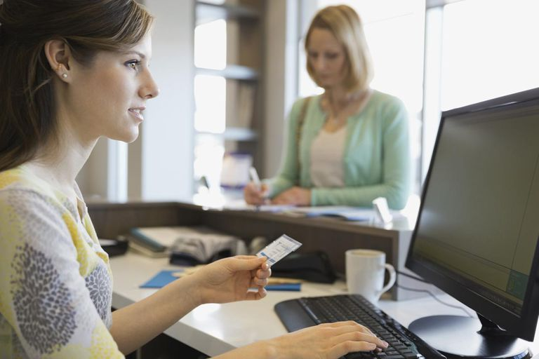 Receptionist inputting insurance information into a computer