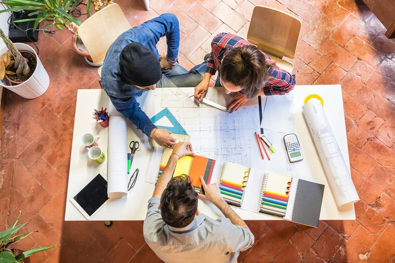 overhead photo of young architects at a table filled with architectural tools