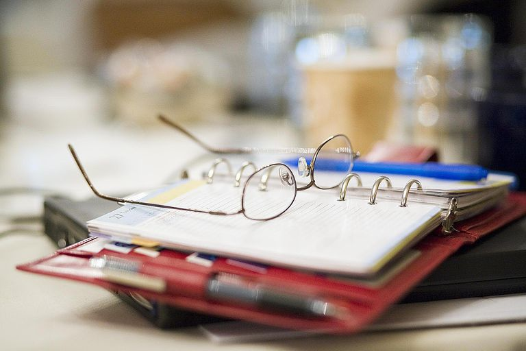Eyeglasses on planner at business meeting